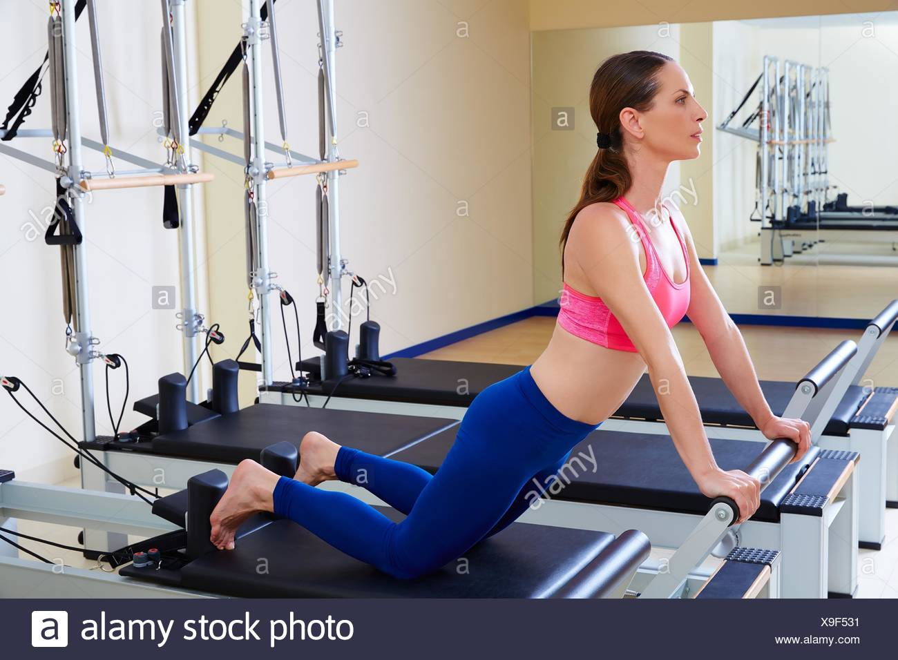Pilates reformer woman down stretch exercise workout at gym indoor. - Stock Image