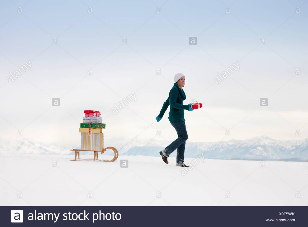 Woman pulls Christmas presents on sled - Stock Image