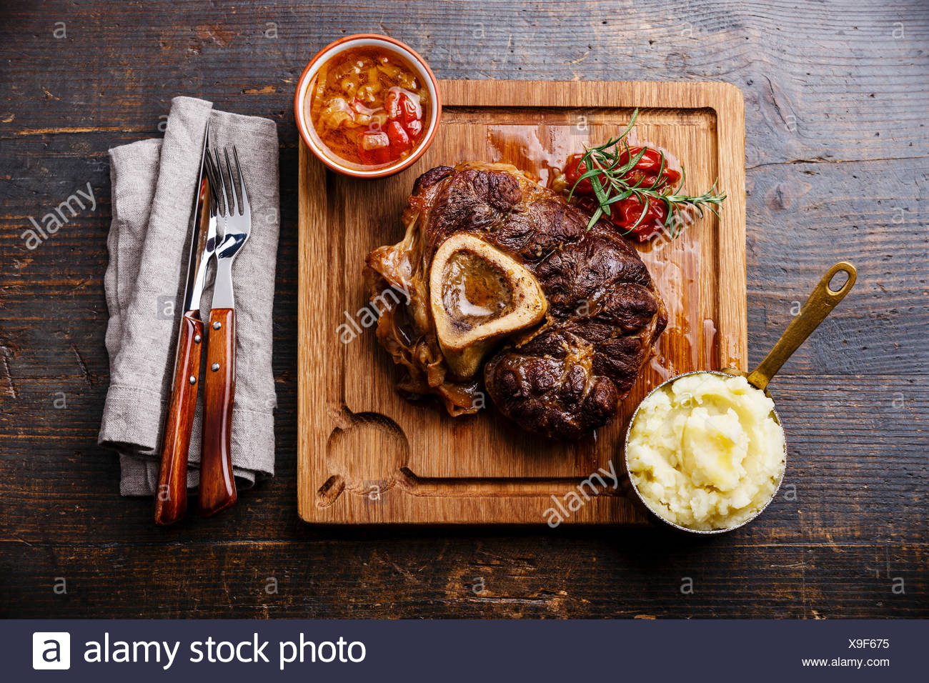 Prepared Osso buco Veal shank with tomatoes and mashed potatoes on serving board on wooden background - Stock Image
