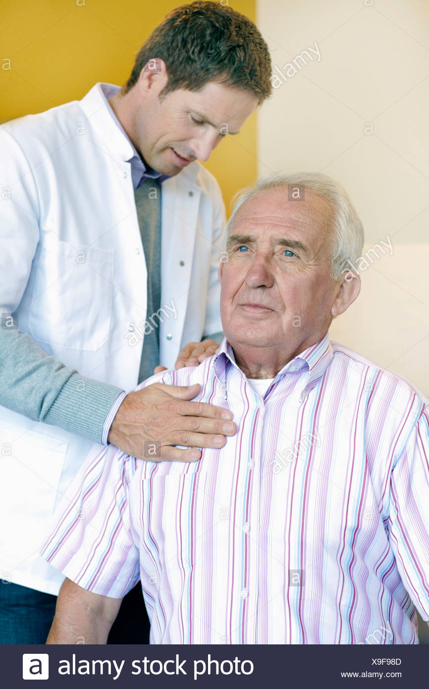 A doctor examining a senior mans shoulder and back - Stock Image