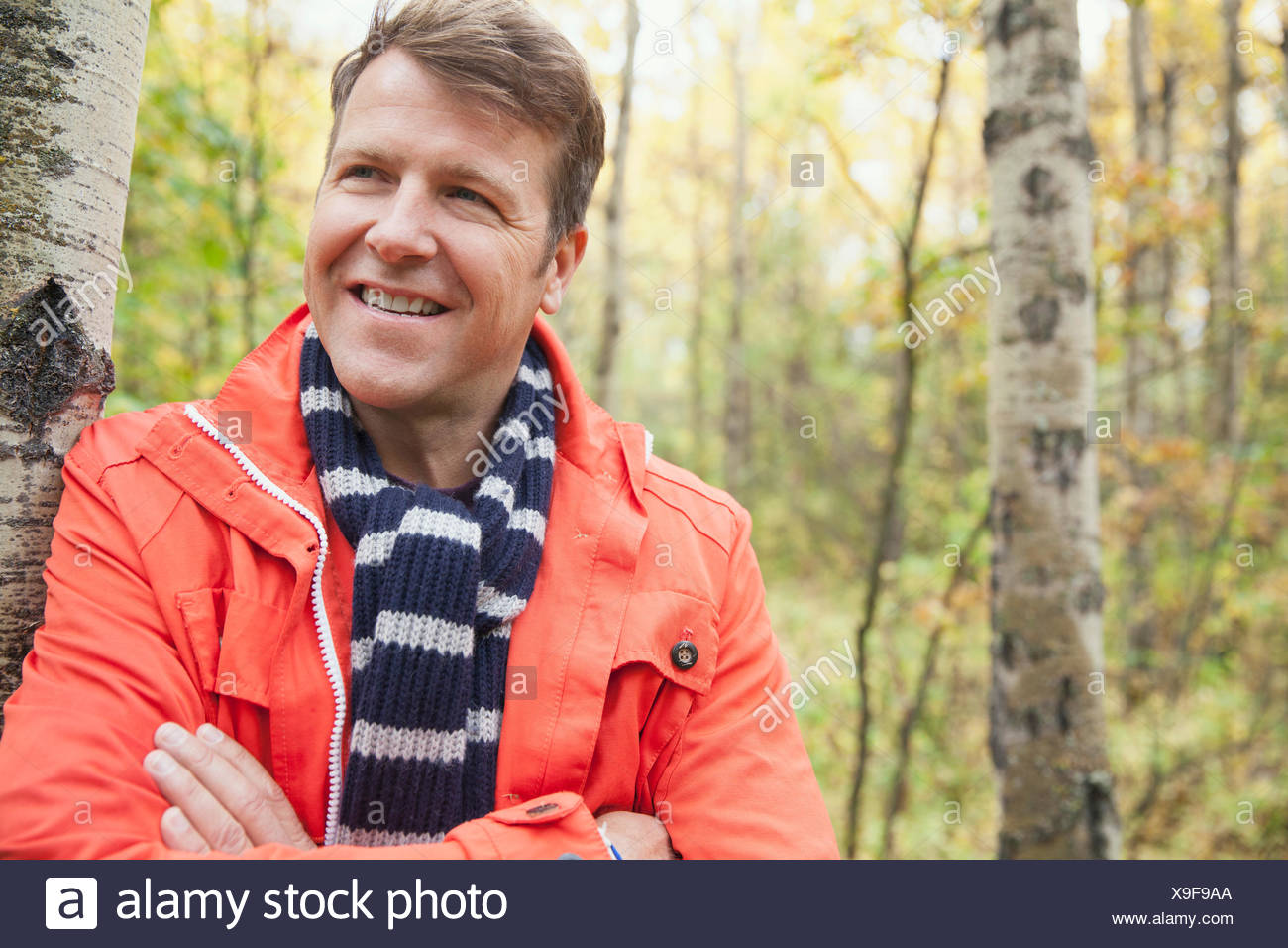 Thoughtful mature man with arms crossed at park - Stock Image