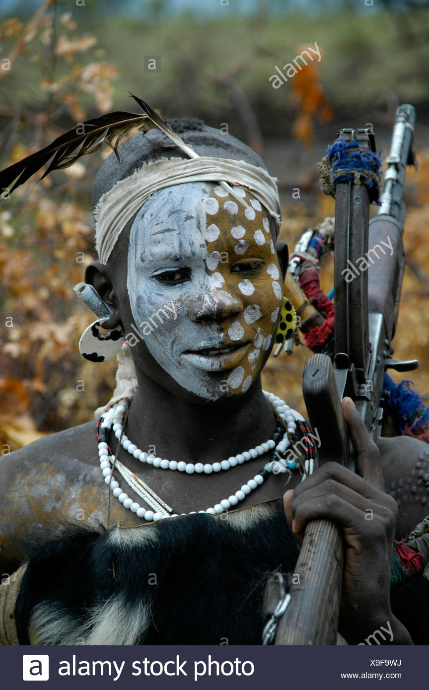 Young man of the Mursi tribe with a painted face shouldering a Kalaschnikow AK-47 rifle, near Jinka, Ethiopia, Africa - Stock Image