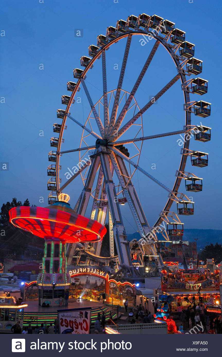 Ferris wheel and swing carousel at a fair in Stuttgart, Baden-Wuerttemberg, Germany, Europe Stock Photo