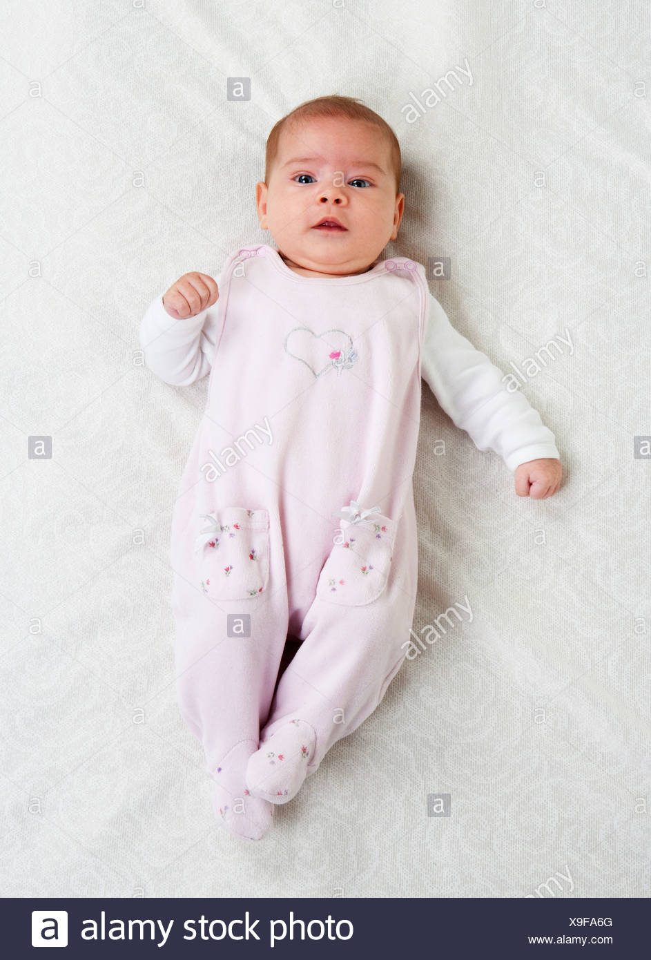Female baby wearing pink rompers lying on white cloth - Stock Image