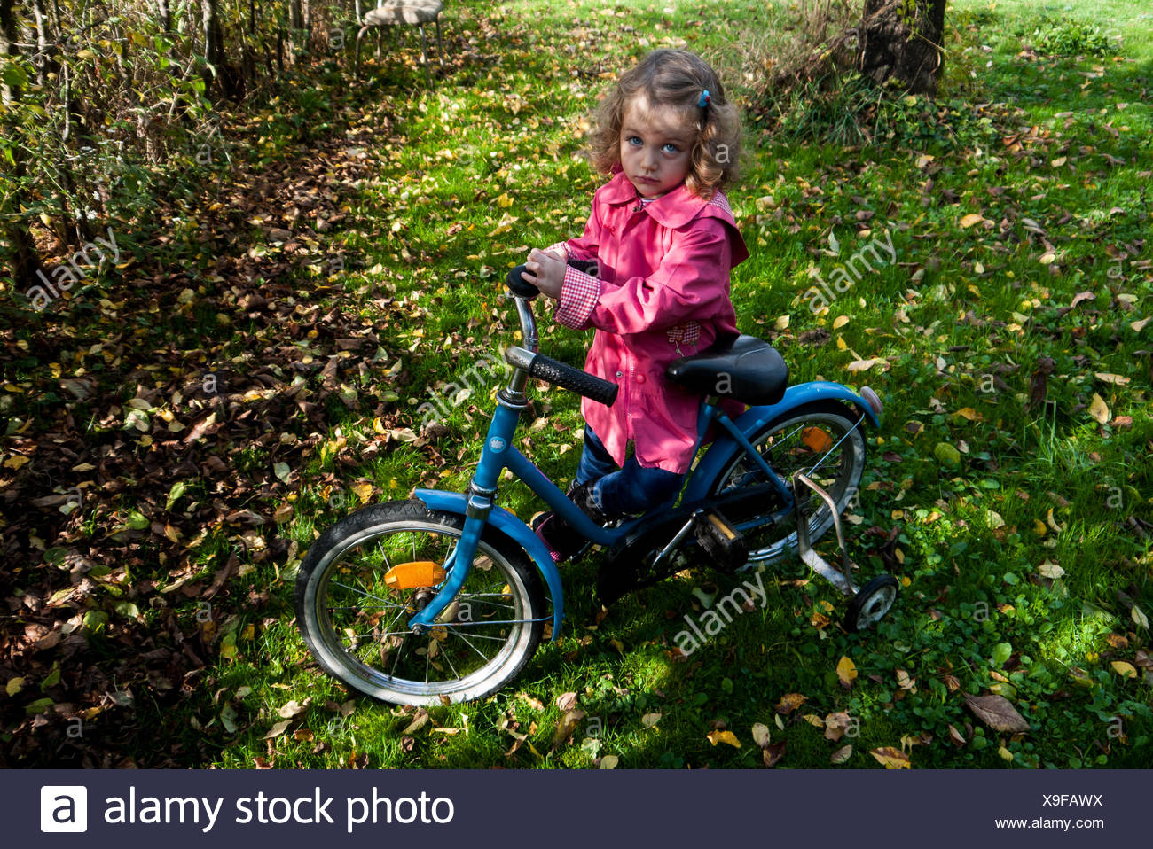 Girl in park with her bicycle - Stock Image