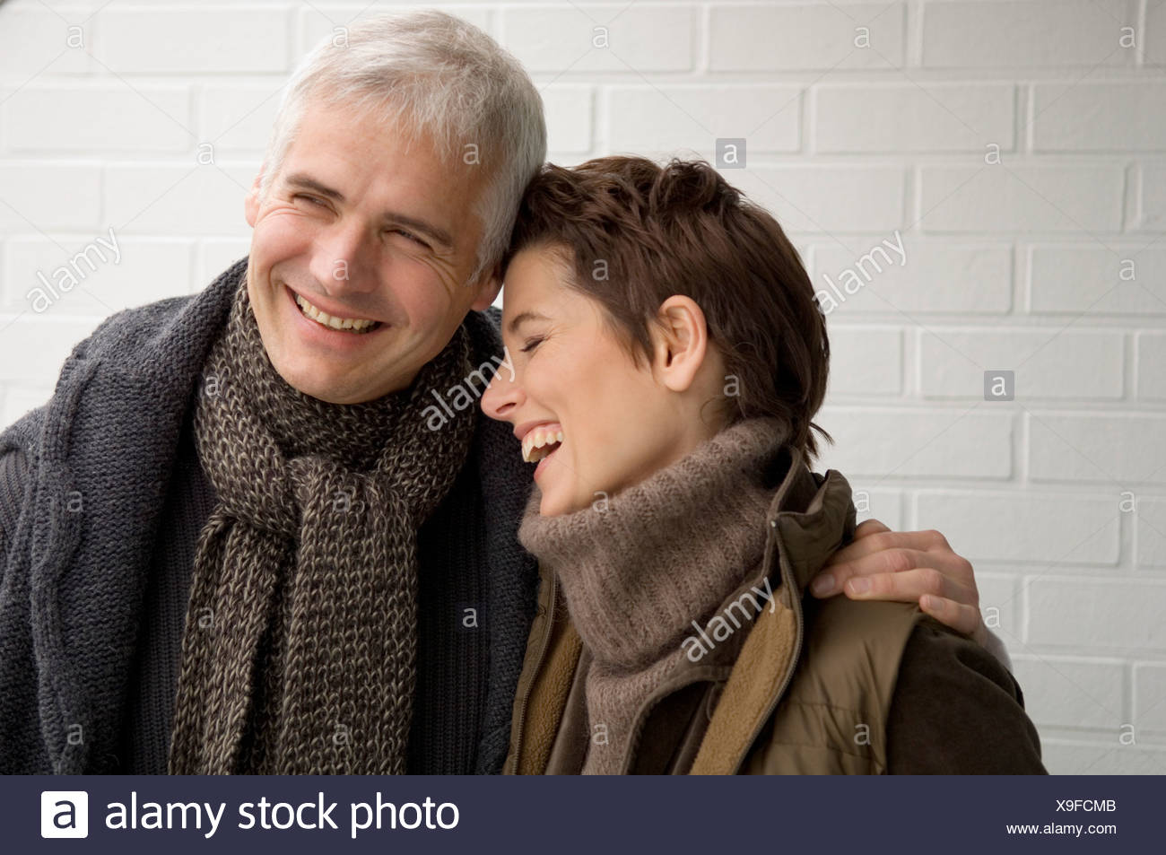 Close-up of a mature man arm around a mid adult woman and smiling - Stock Image