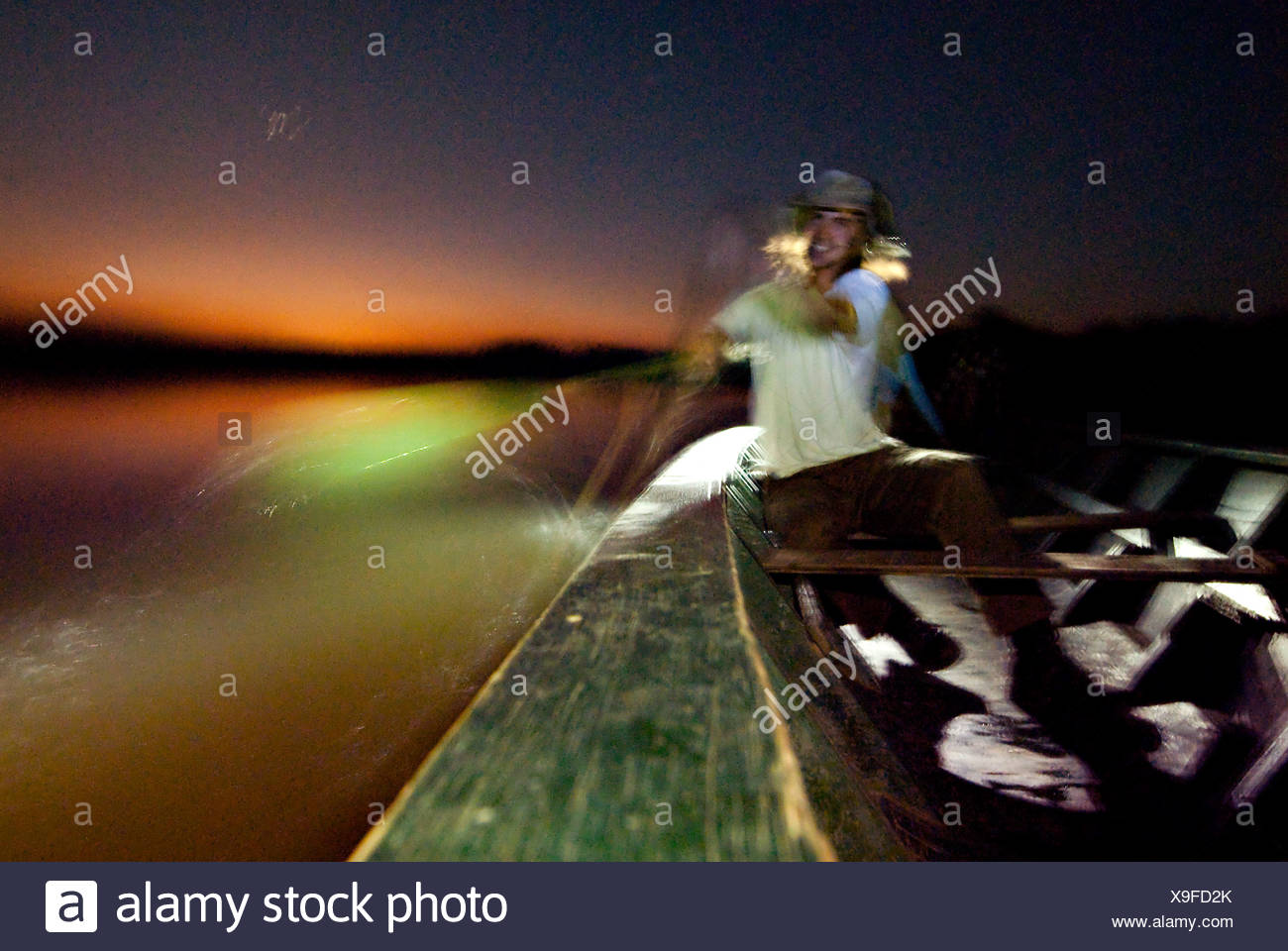 Dorian SImon paddles a large wooden canoe at sunset in sandoval lake. - Stock Image