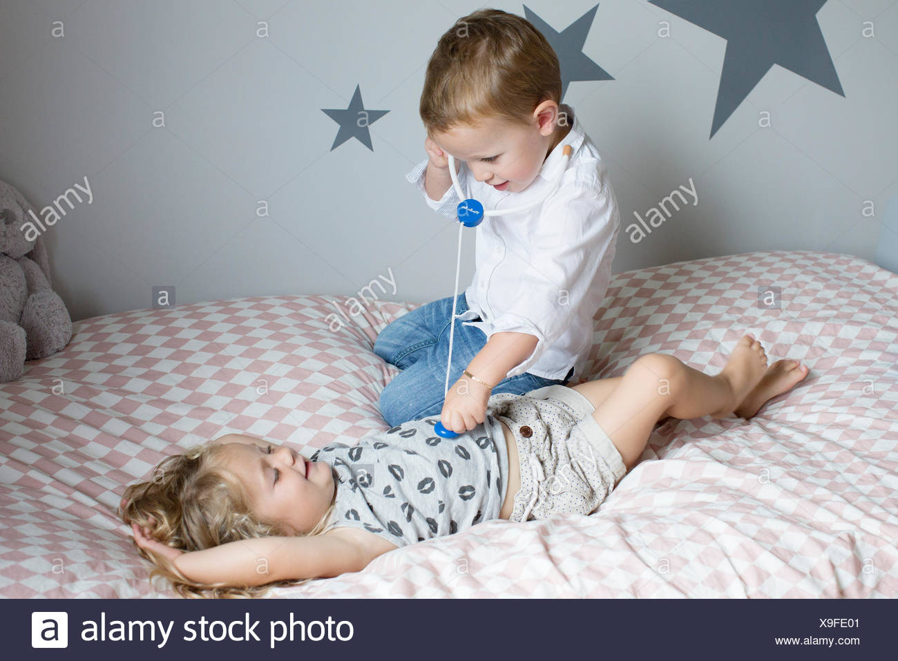 Children playing doctor with toy stethoscope - Stock Image