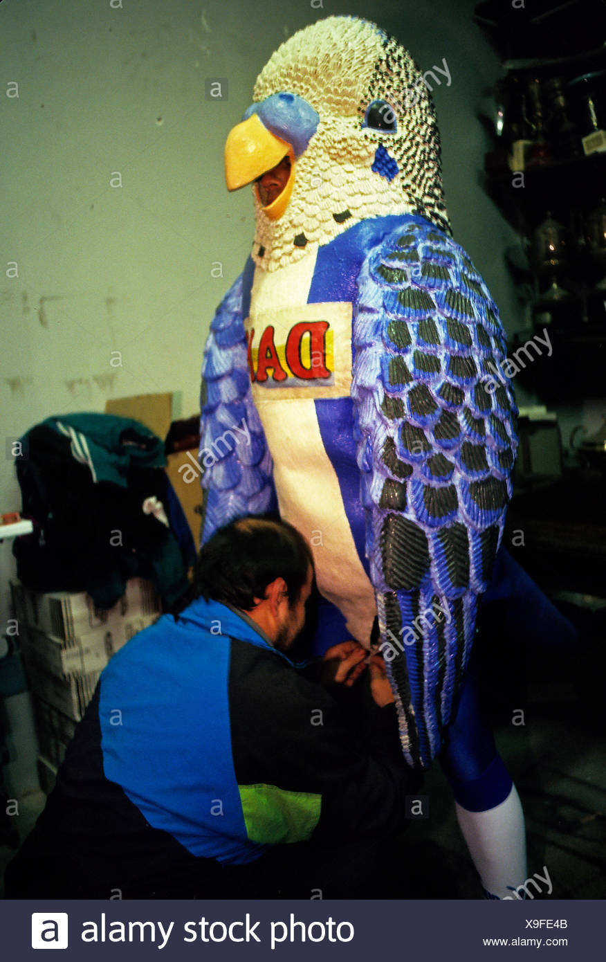 A man buttons up the RDC Espanol Football Club mascot costume on a man. - Stock Image