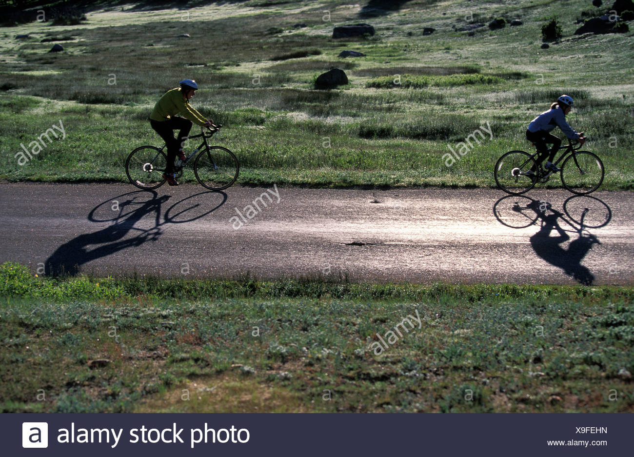 A man and a woman cycling on a country road. - Stock Image