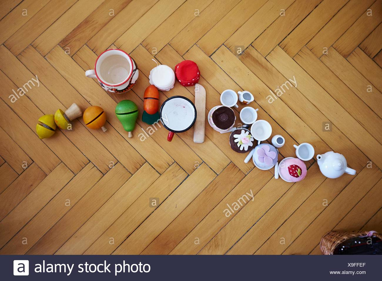 Overhead view of cupcakes, toys and cups on parquet floor - Stock Image