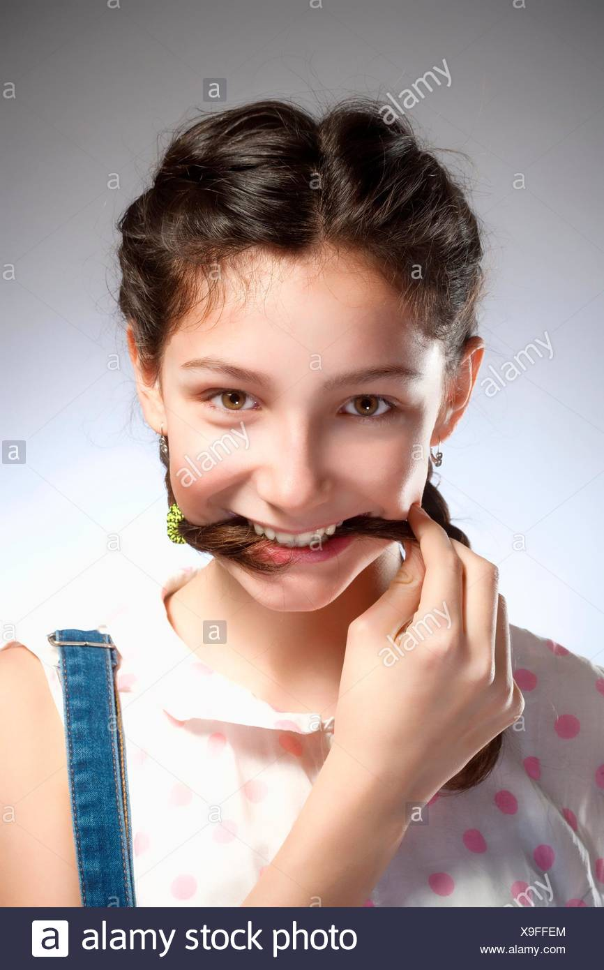 Portrait of a Preadolescent Girl with Biting Brait. - Stock Image