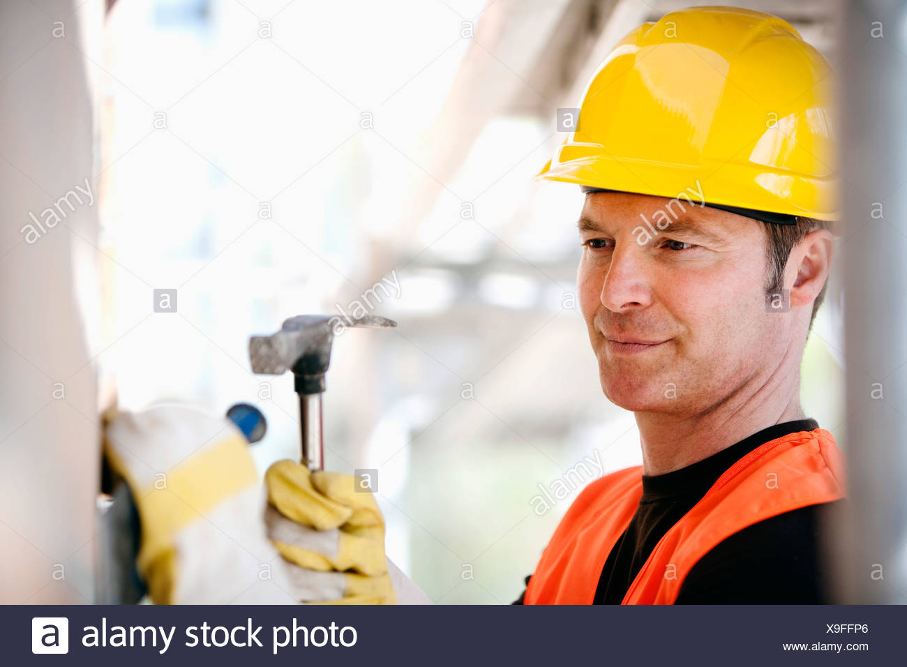 portrait of construction worker using hammer and chisel - Stock Image