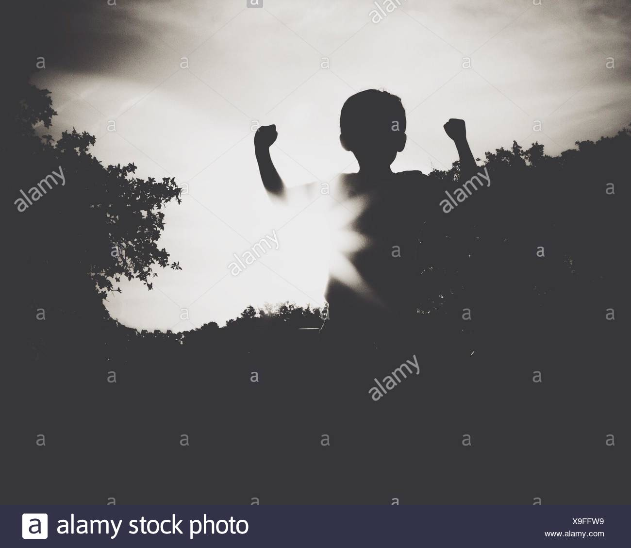 Silhouette Boy Flexing Biceps Against The Sky - Stock Image