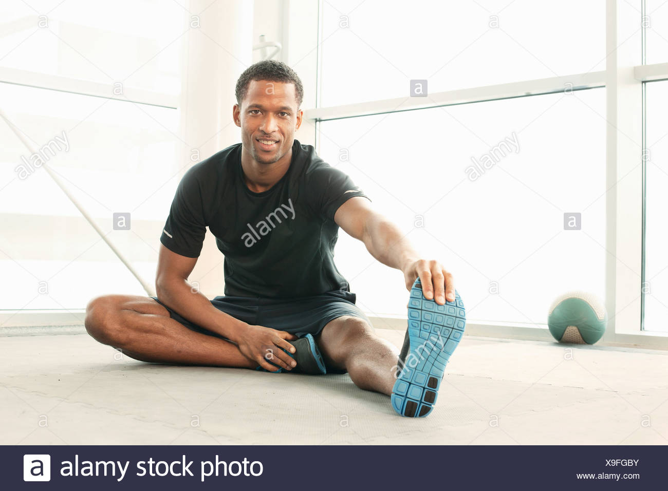 Man sitting touching toes stretching - Stock Image