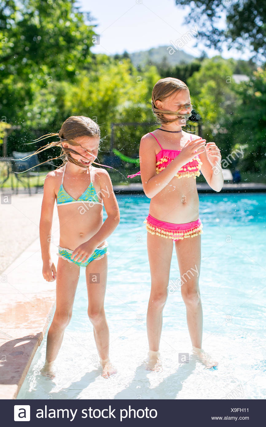 Two sisters shaking wet hair by outdoor swimming pool - Stock Image