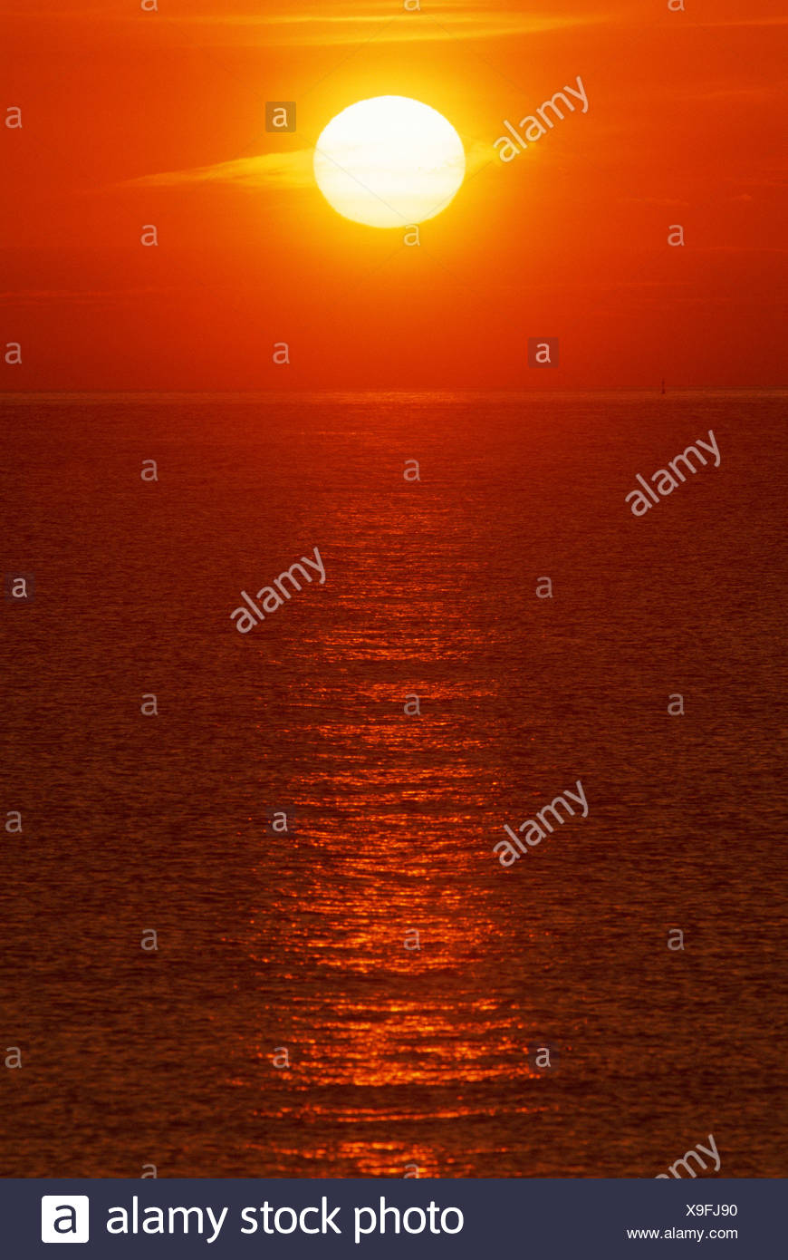 Sun setting over sea with reflections in water Spain - Stock Image