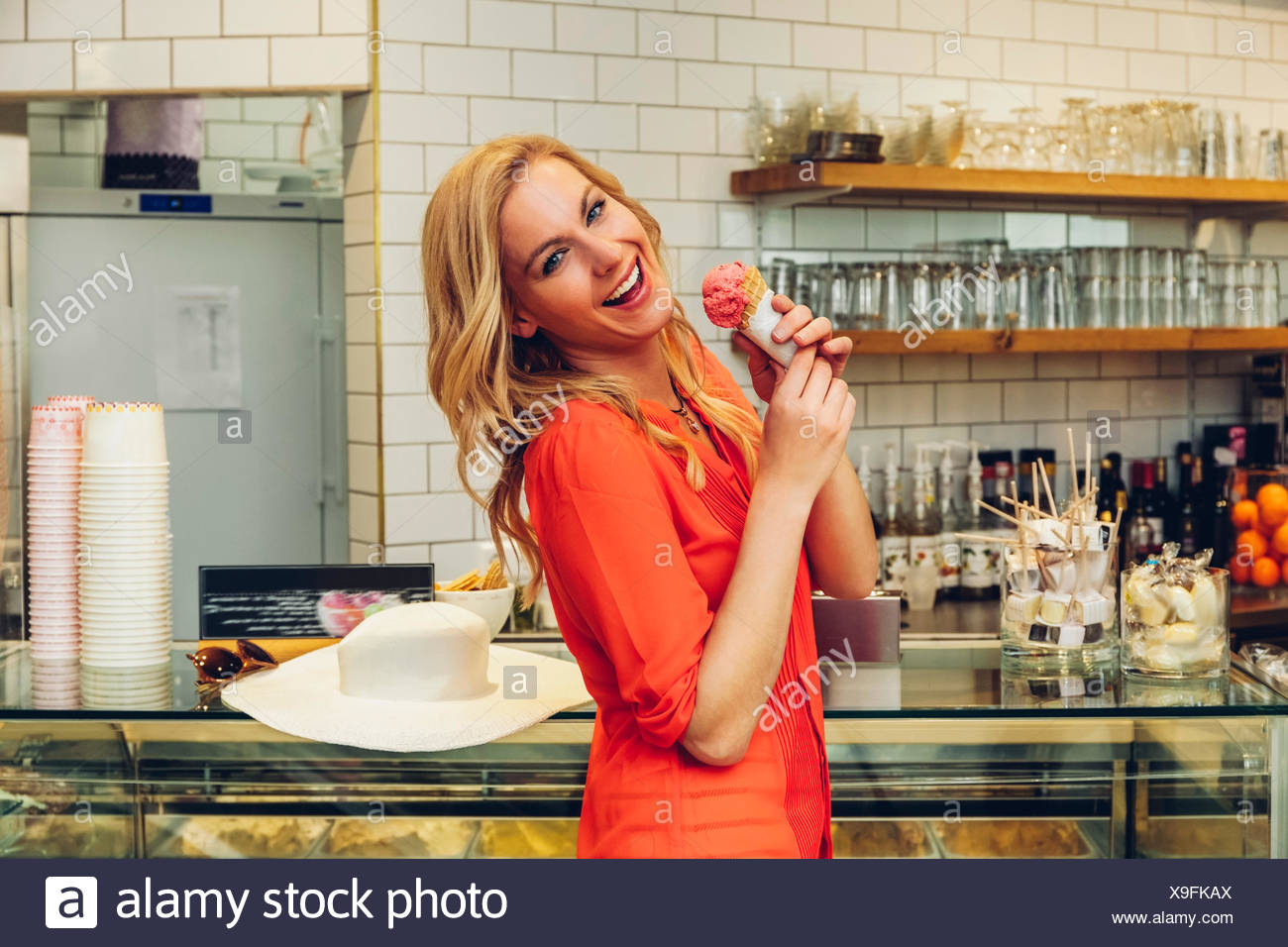 Portrait of laughing blond woman standing at counter in a ice cream parlour with ice cream cone - Stock Image