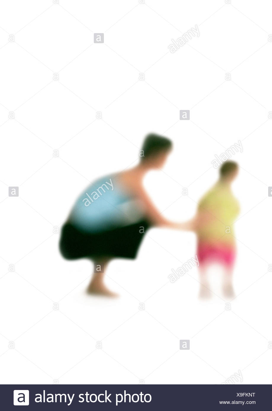 Silhouette of woman squatting down next to child, on white background, defocused - Stock Image