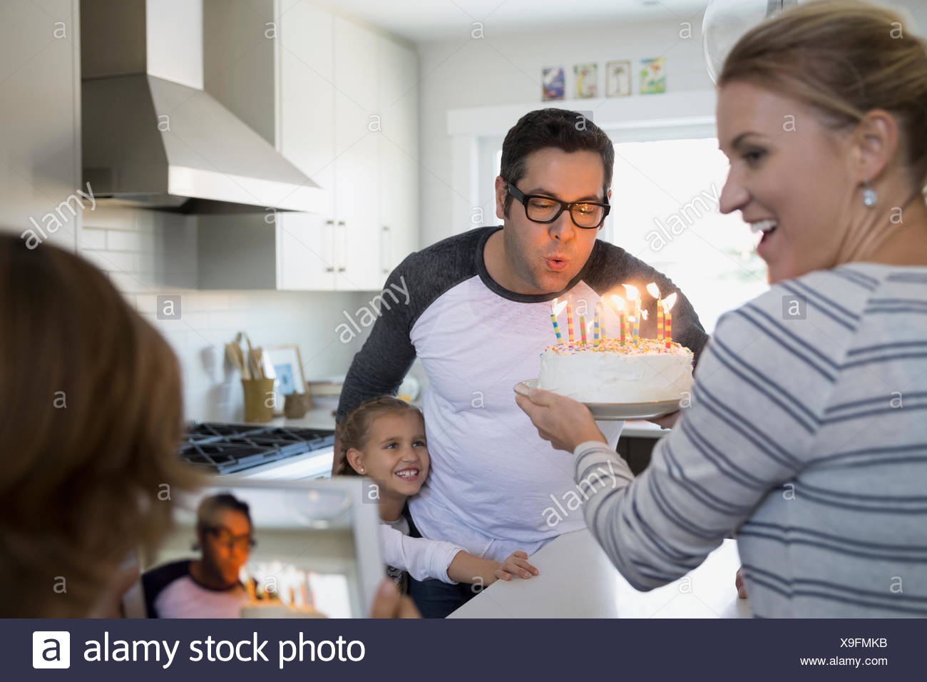 Father blowing out birthday cake candles in kitchen - Stock Image