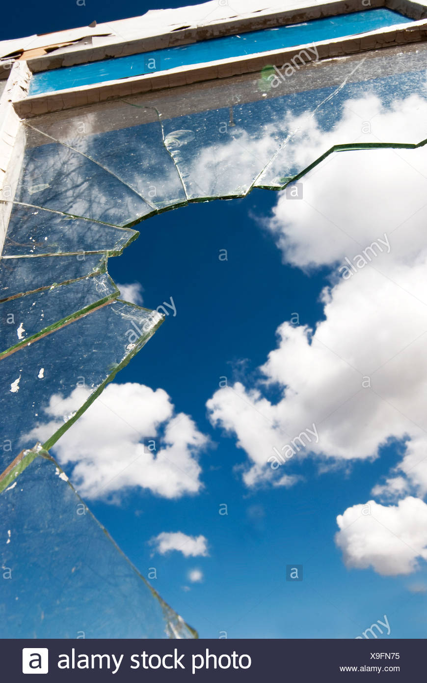 Close up of jagged broken window with blue sky in background - Stock Image