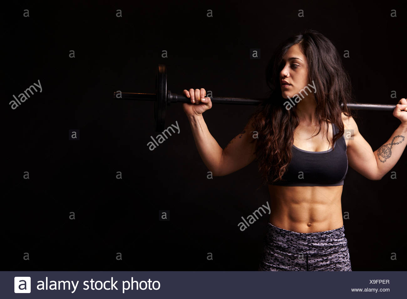 Muscular dark haired woman holding barbell on her shoulders - Stock Image