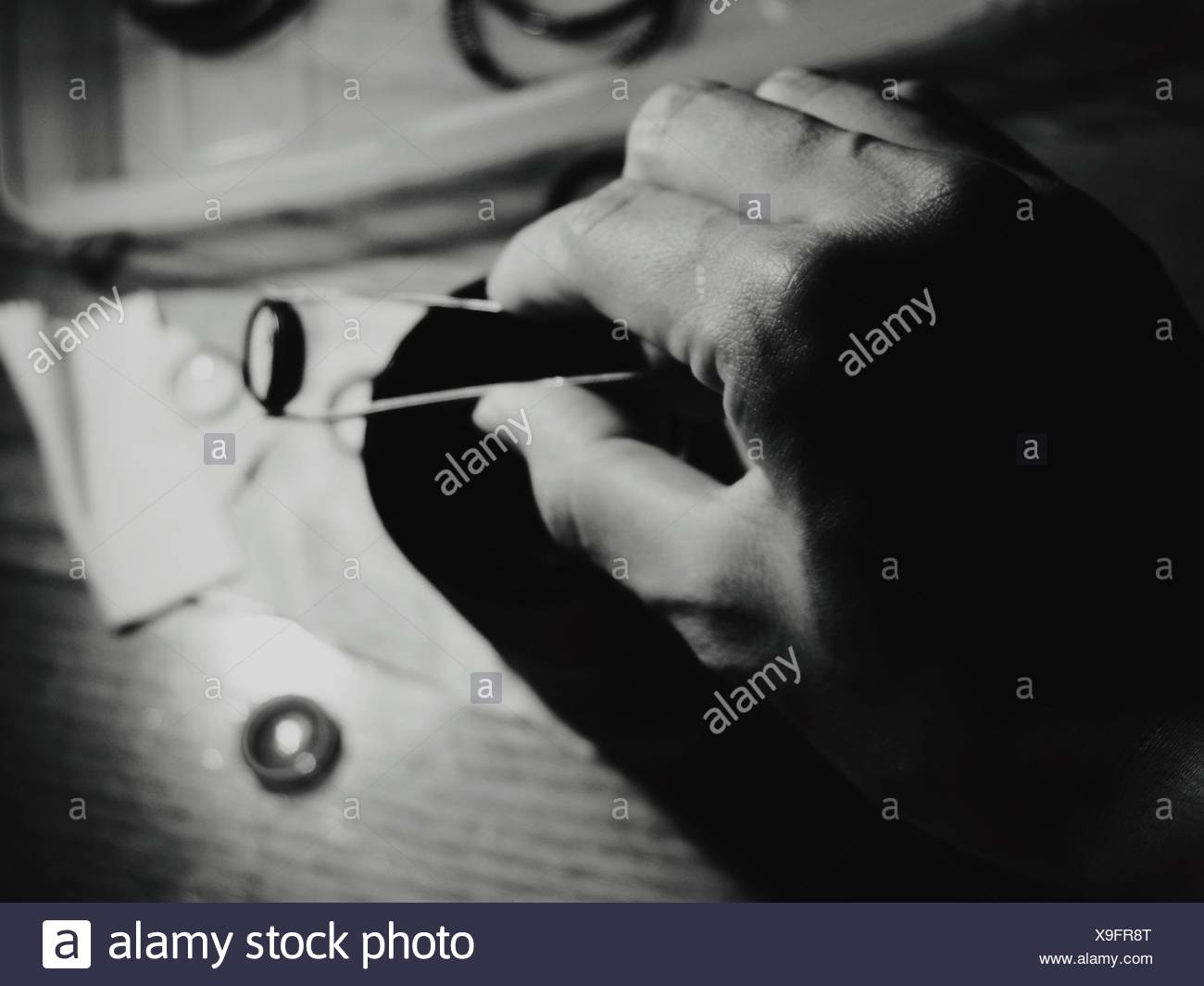 Cropped Hand Holding Button With Tongs - Stock Image