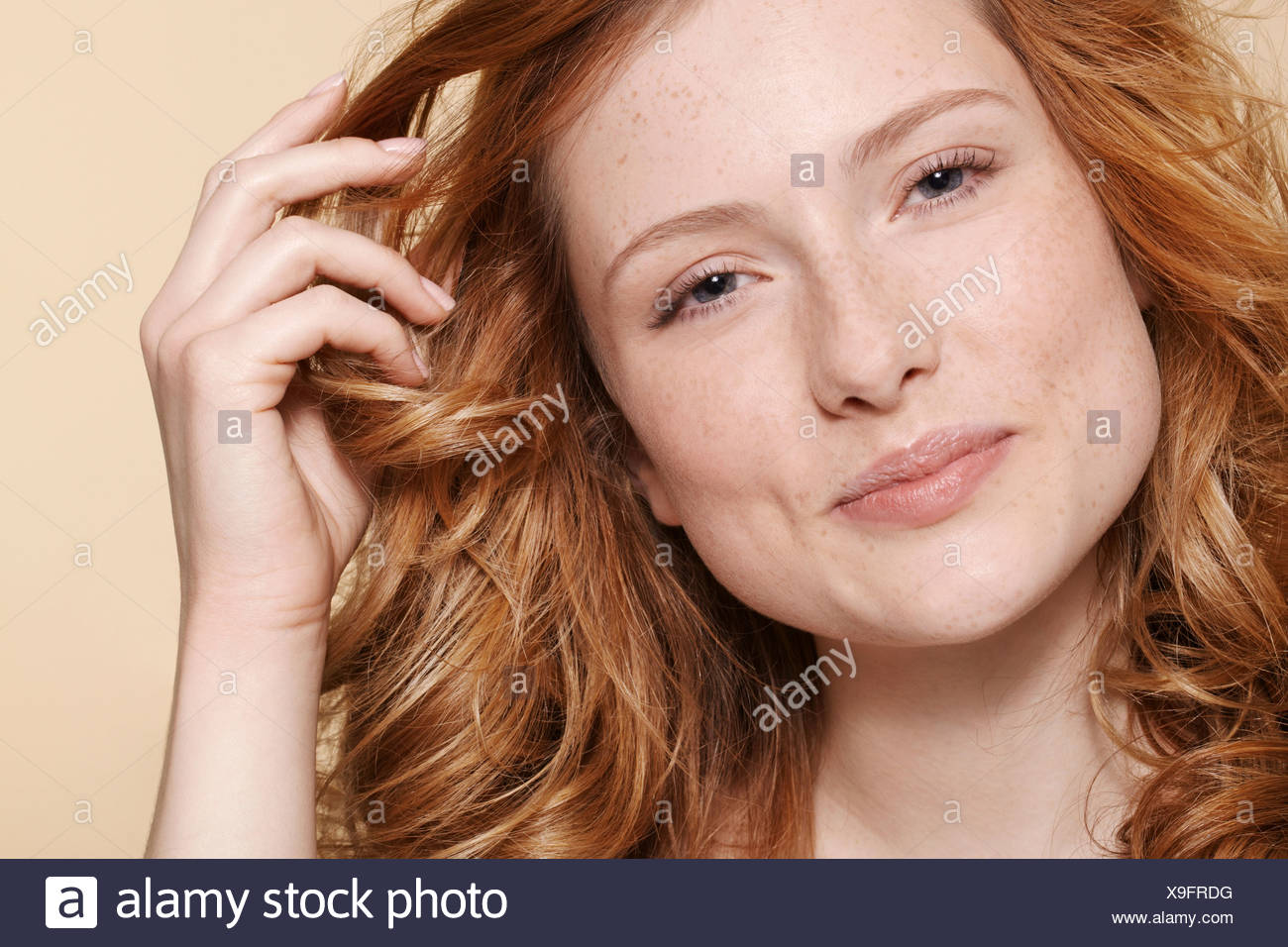 Studio shot of young woman with curly red hair, hand in hair - Stock Image
