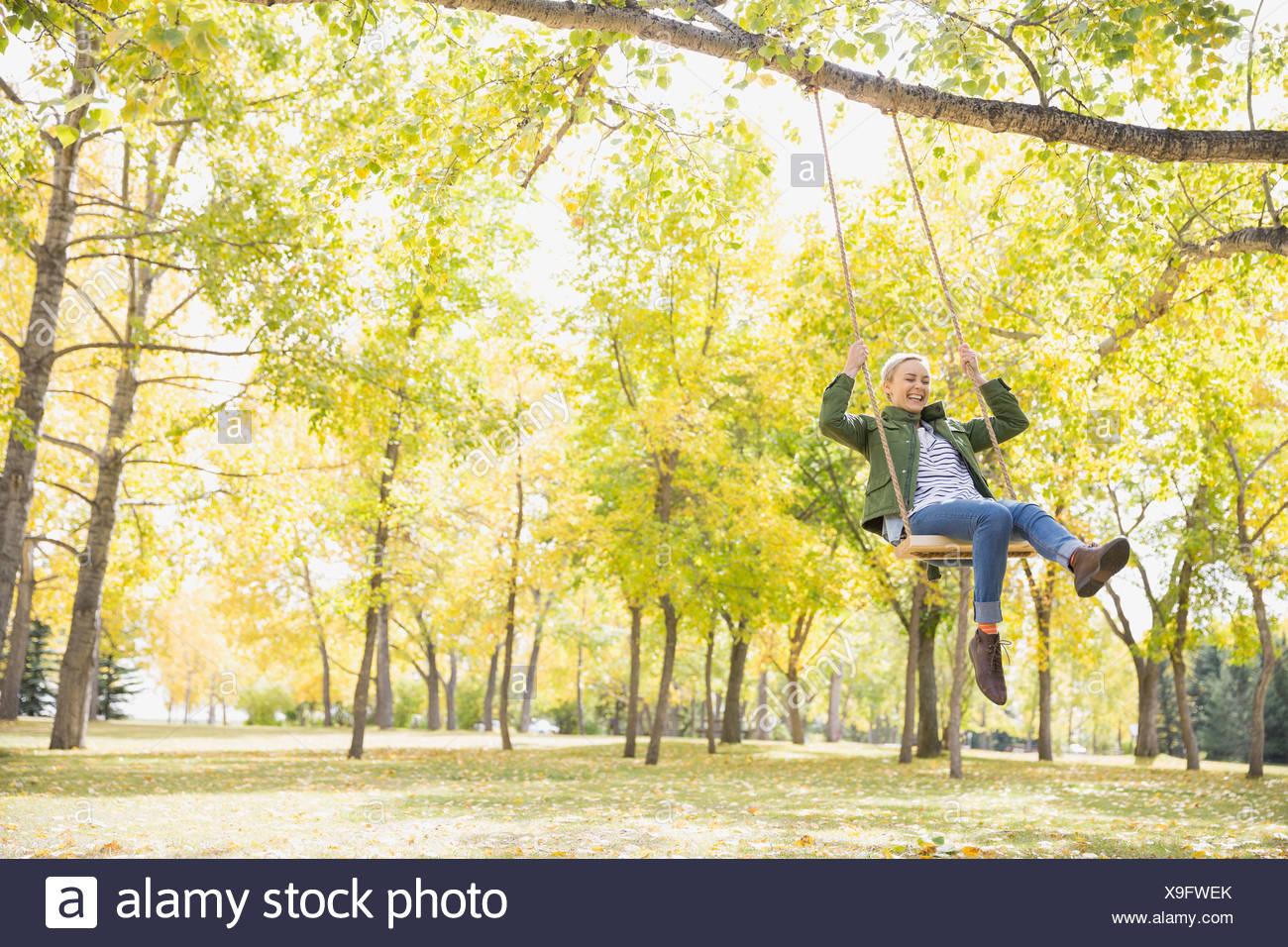 Playful woman swinging - Stock Image