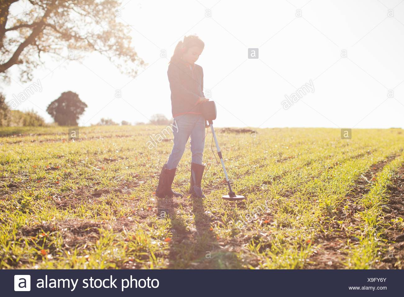 Girl wearing headphones searching with metal detector in sunlit field - Stock Image