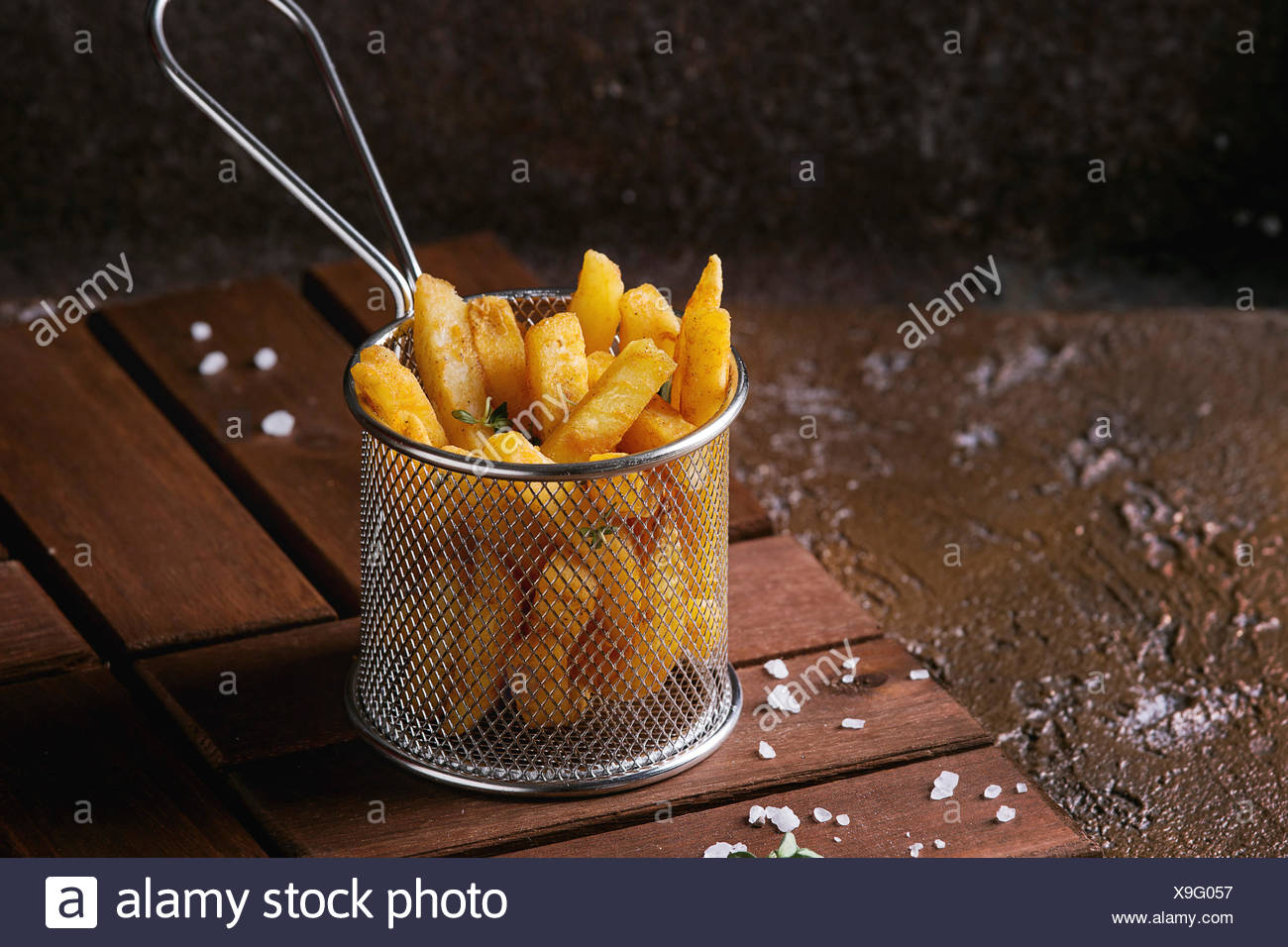 Traditional french fries potatoes served in frying basket with salt, thyme on wooden board over brown texture background. Homemade fast food - Stock Image