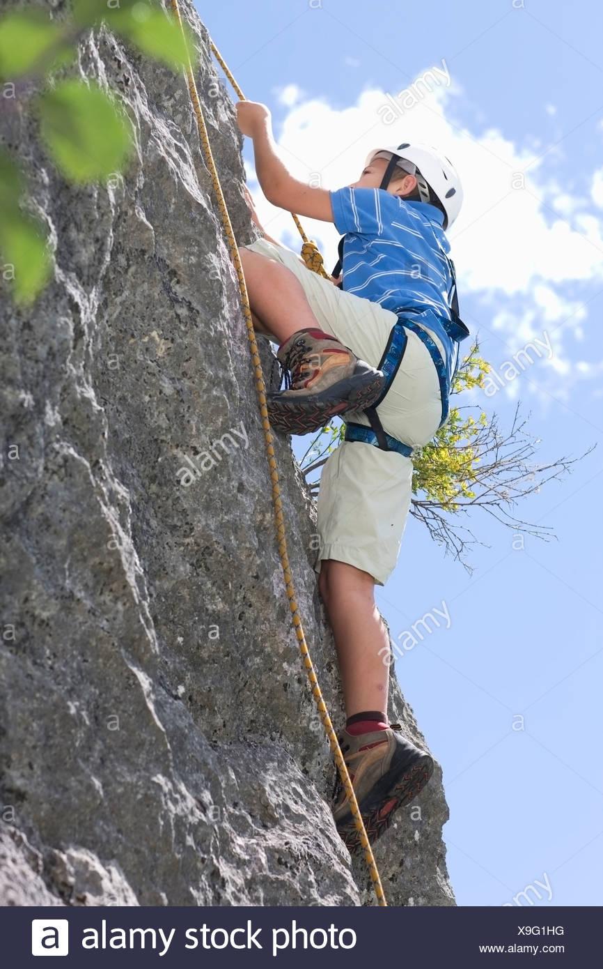 Boy climbing up a hill - Stock Image