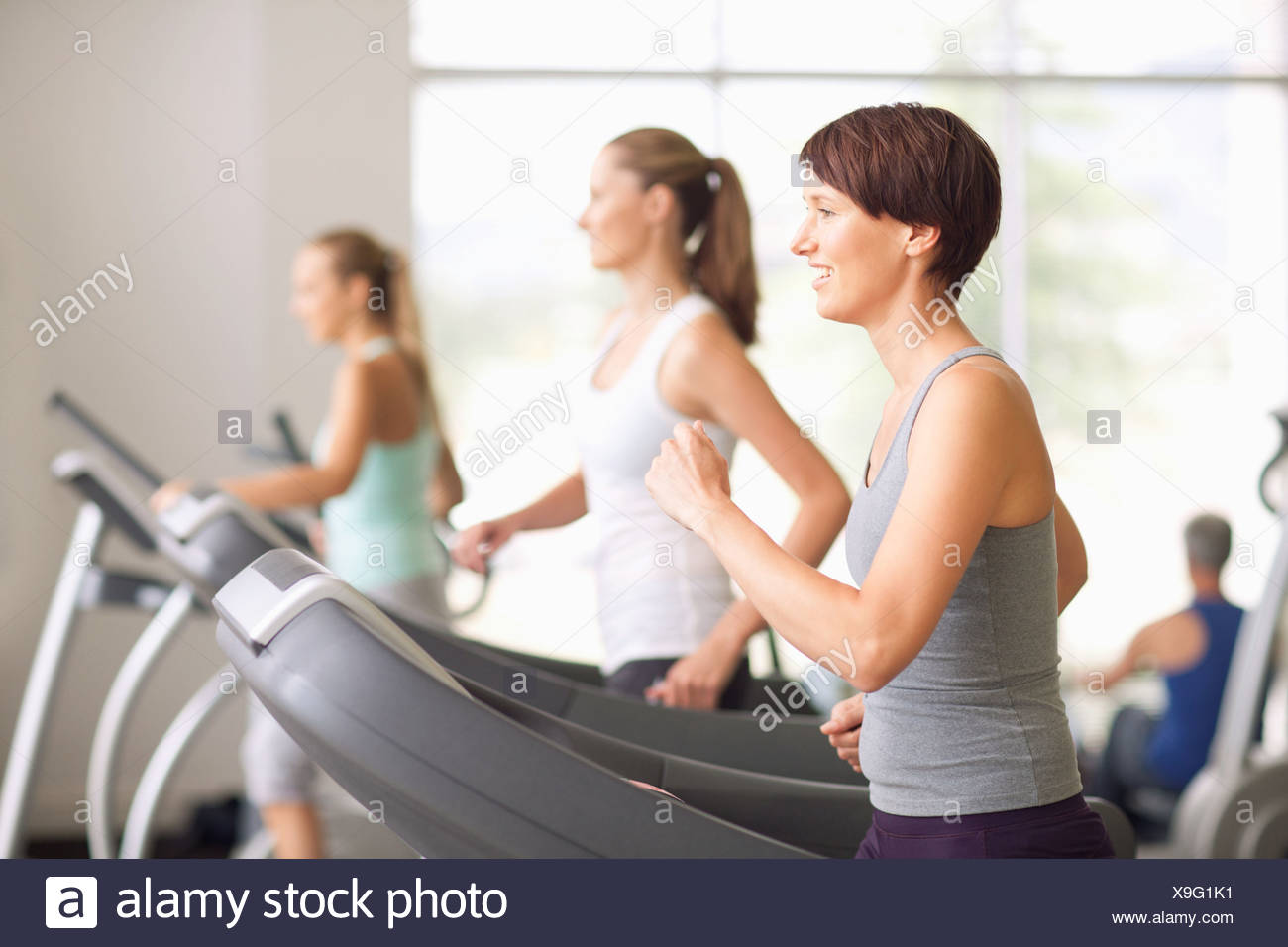 Portrait of smiling women running on treadmills in gymnasium - Stock Image