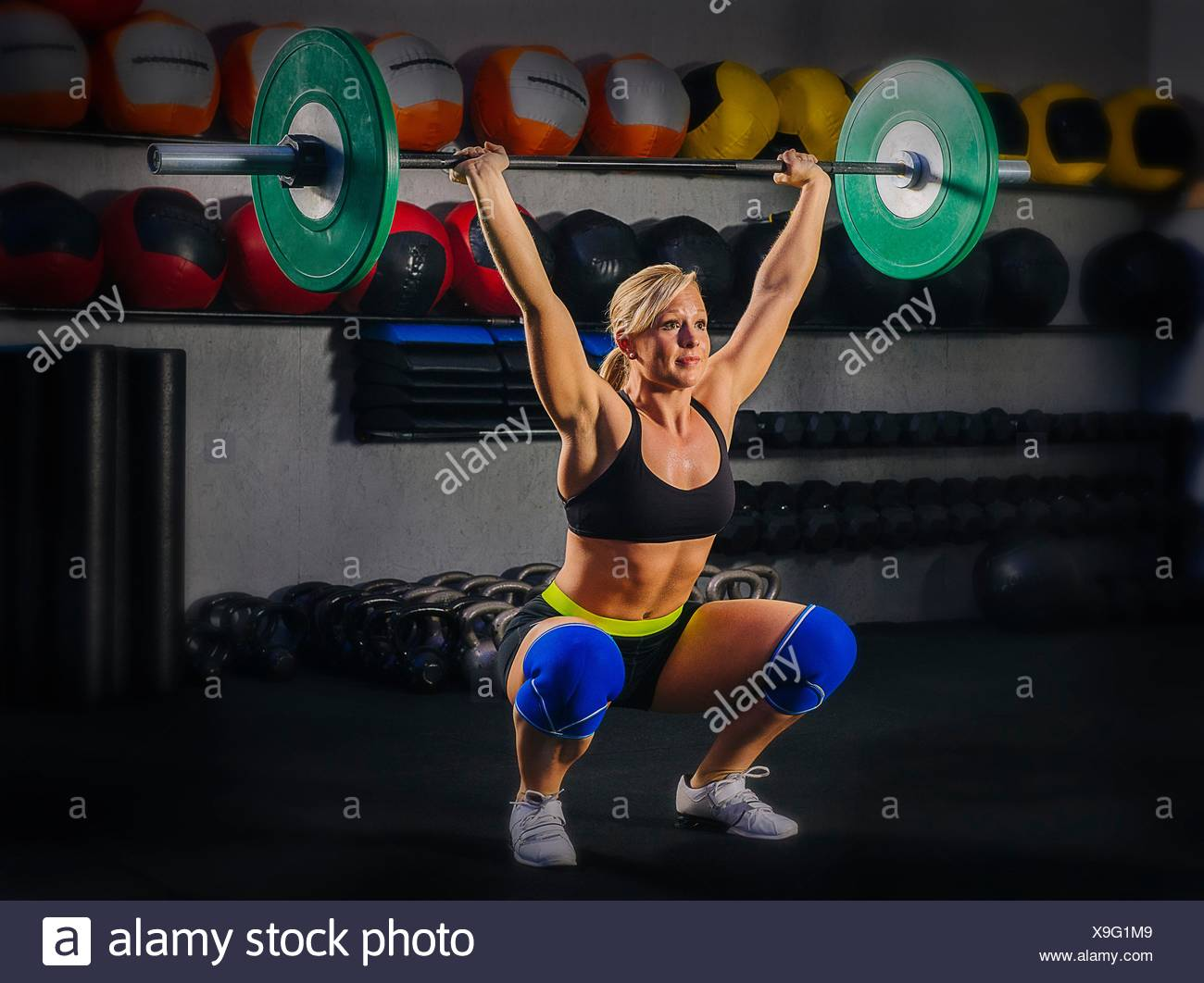 Young woman squatting with barbell raised in gym - Stock Image