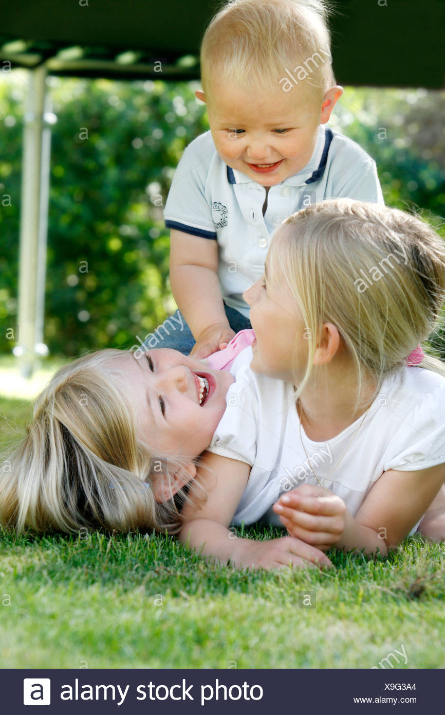 Three blond siblings playing in the garden, Sweden. - Stock Image