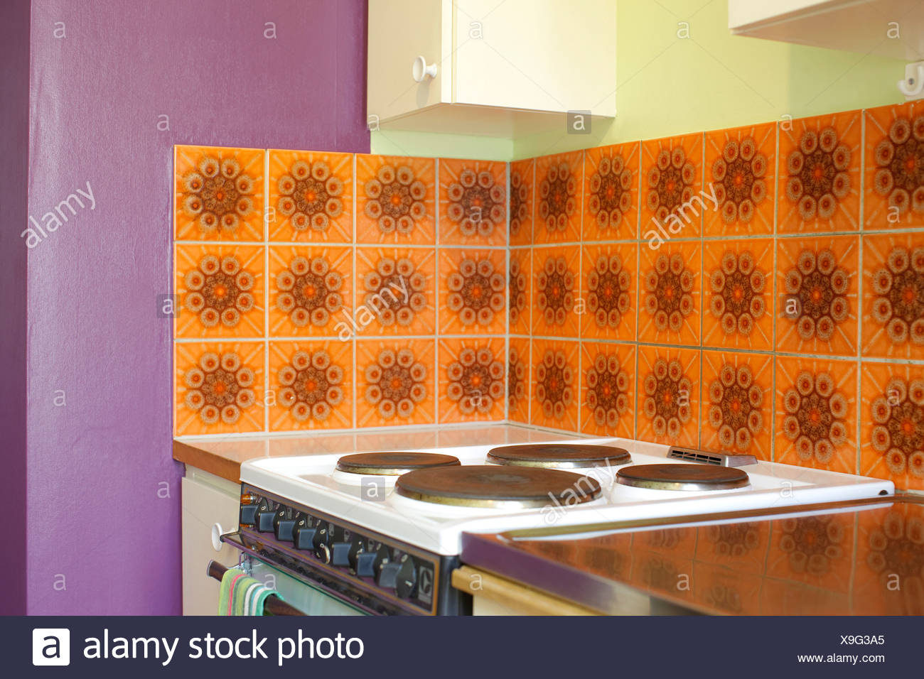 View of stove against tiled and purple walls in the kitchen - Stock Image