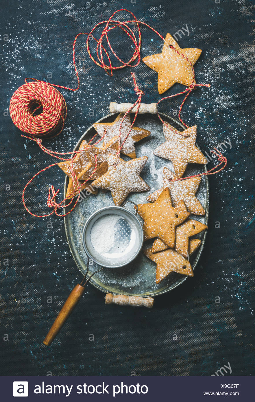 Christmas holiday star shaped gingerbread cookies for Christmas tree decoration, sieve, decorative snowflakes, balls and toys in Stock Photo