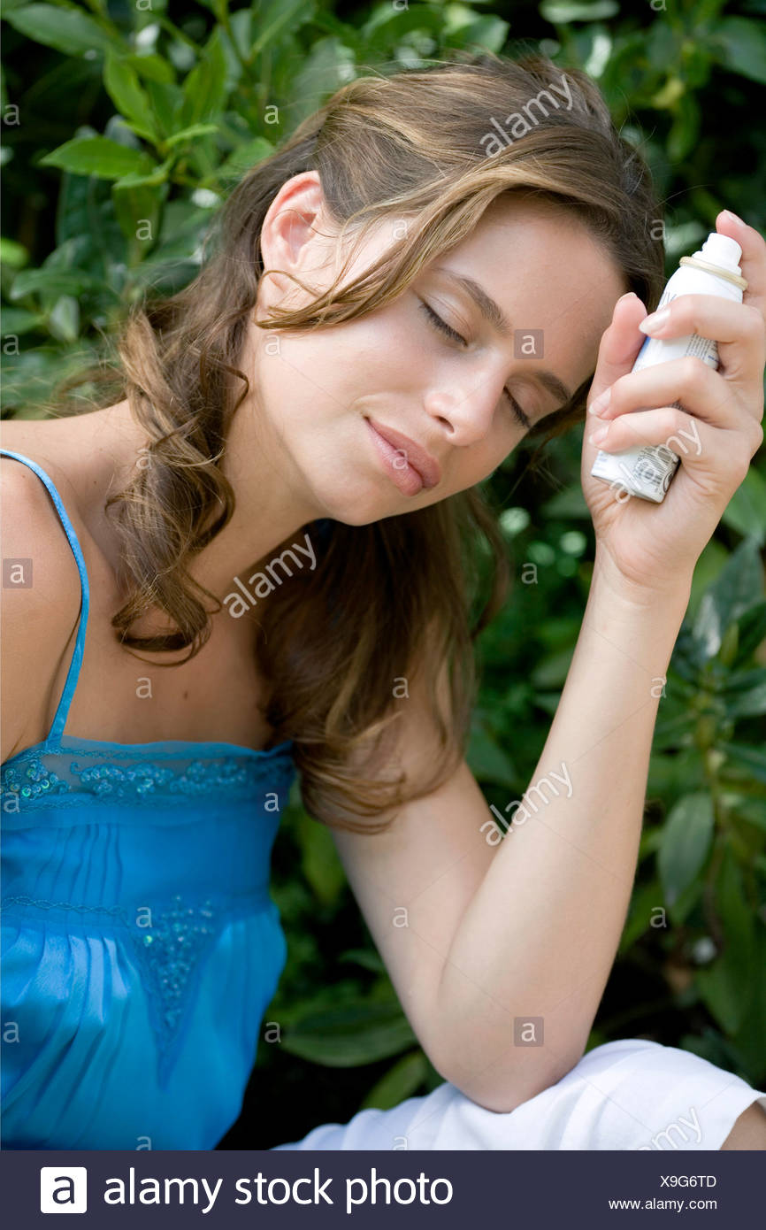 A DayYourself: Female long brunette hair tied back loosely wearing blue top holding small atomiser spray leaning elbow on leg, - Stock Image
