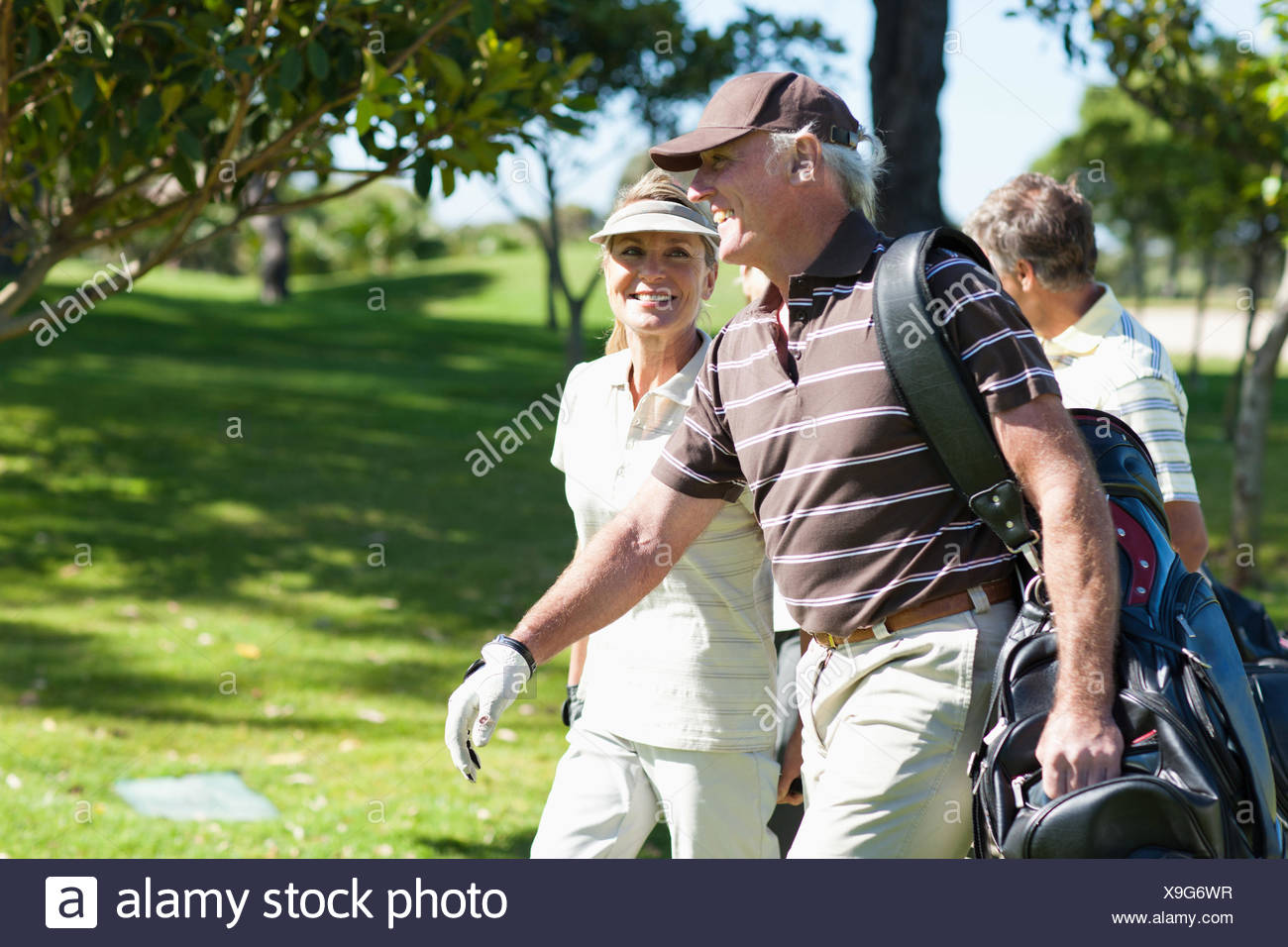 Mature couple carrying golf bags - Stock Image