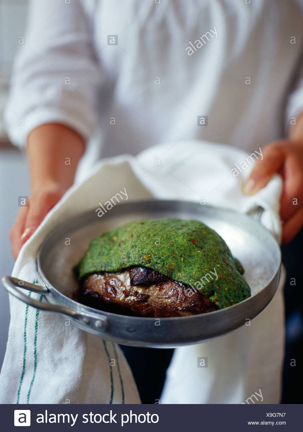 Leg of lamb cooked in a herb crust - Stock Image