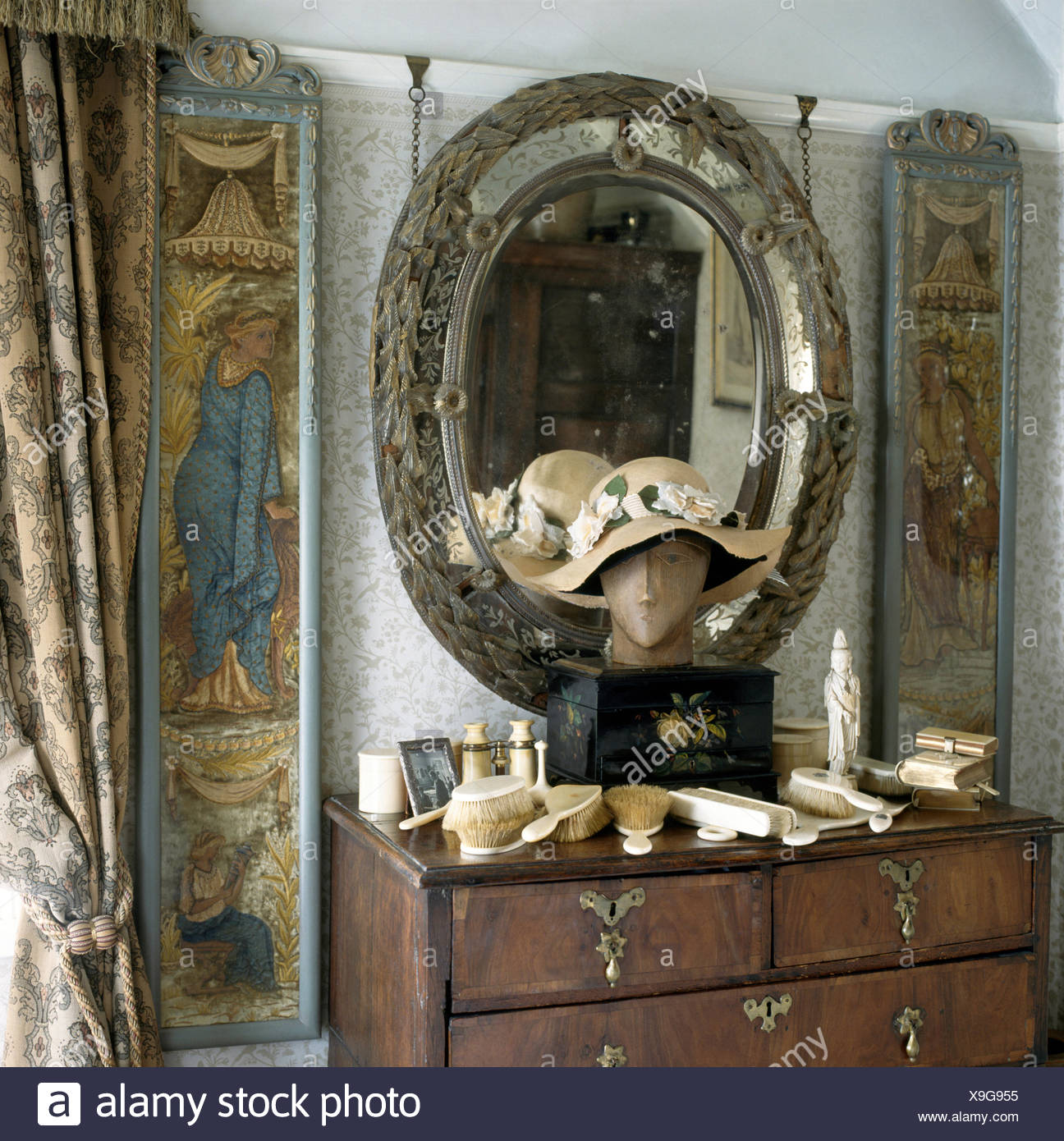Oval antique mirror and medieval panels above chest of drawers with ...