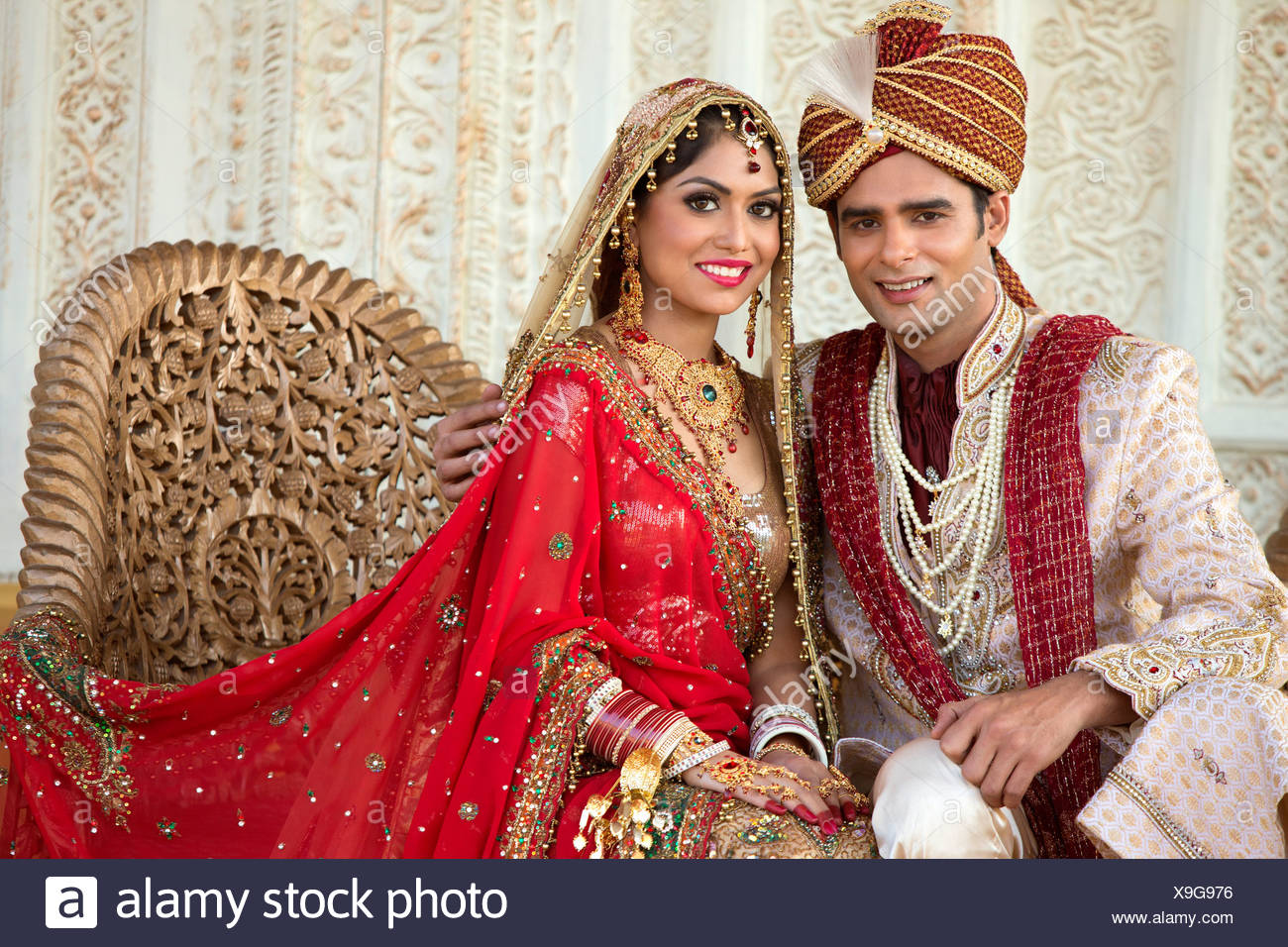 6c515d48fe Indian bride and groom in traditional wedding dress sitting on a couch
