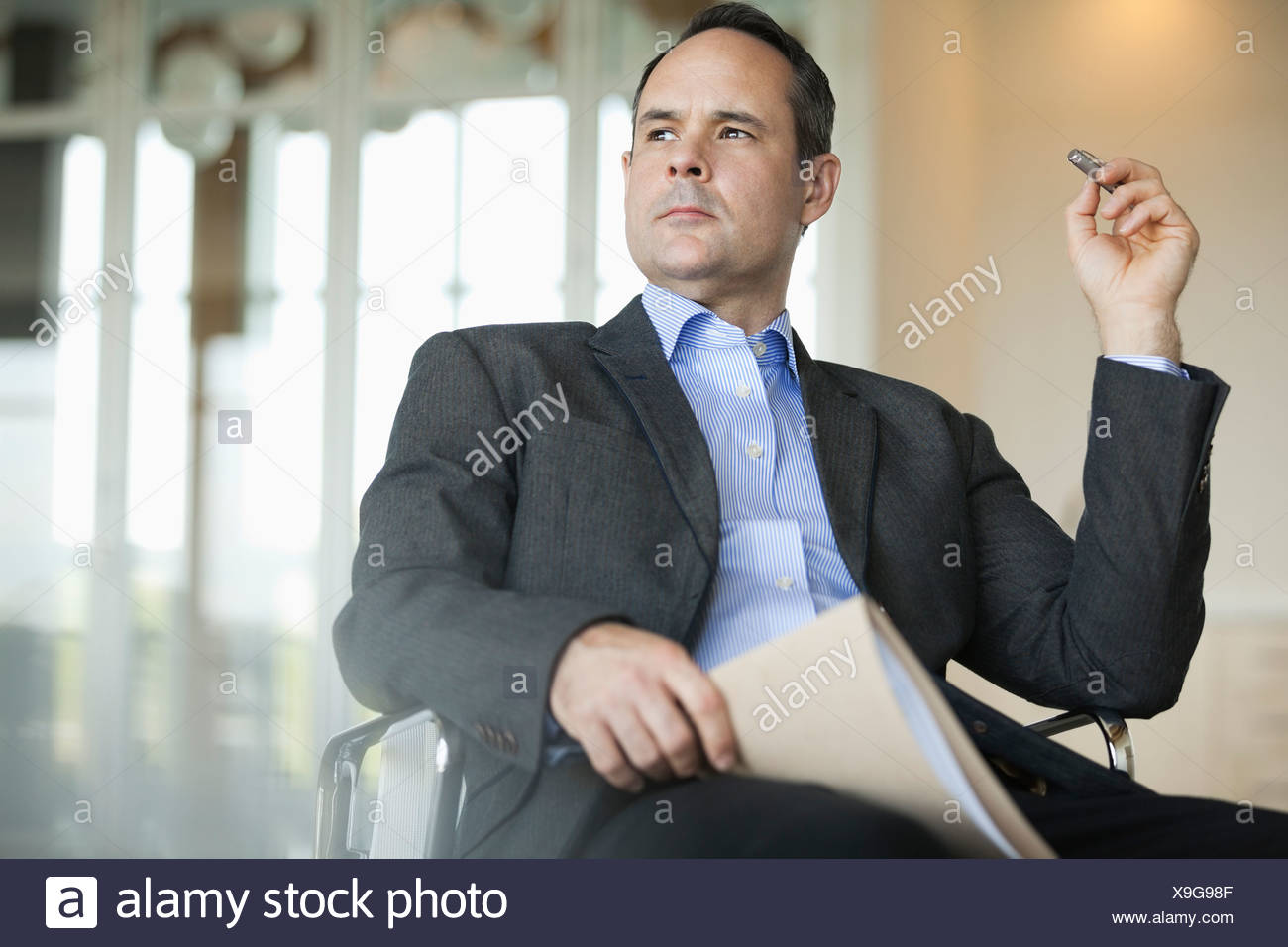 Thoughtful businessman sitting in chair - Stock Image