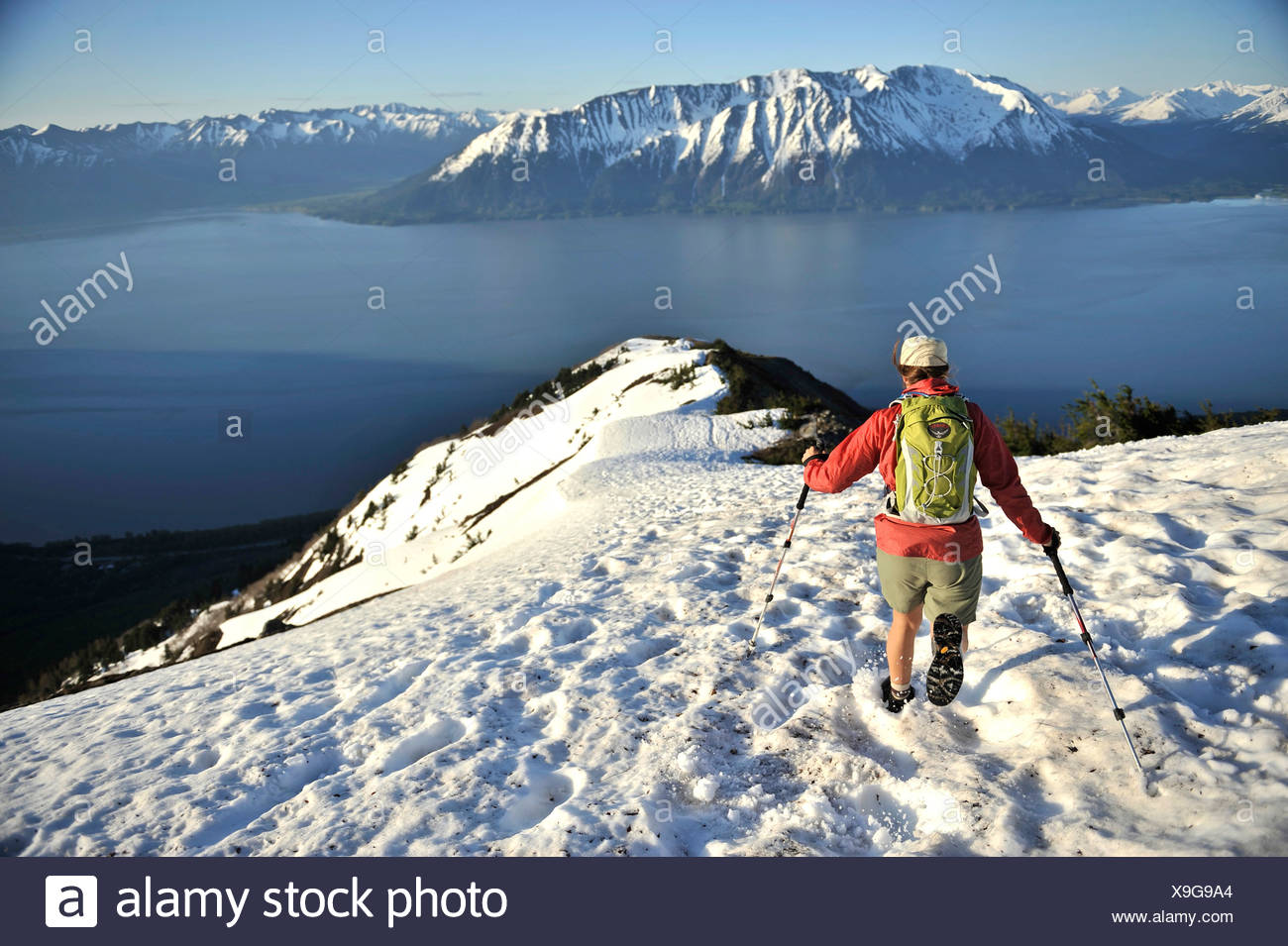 Woman hikes through snow while descending the Bird Ridge Trail above Turnagain Arm in Chugach State Park, Southcentral Alaska - Stock Image