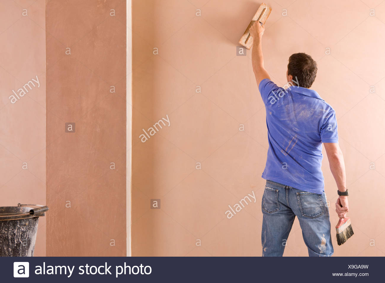Man plastering wall in house Stock Photo