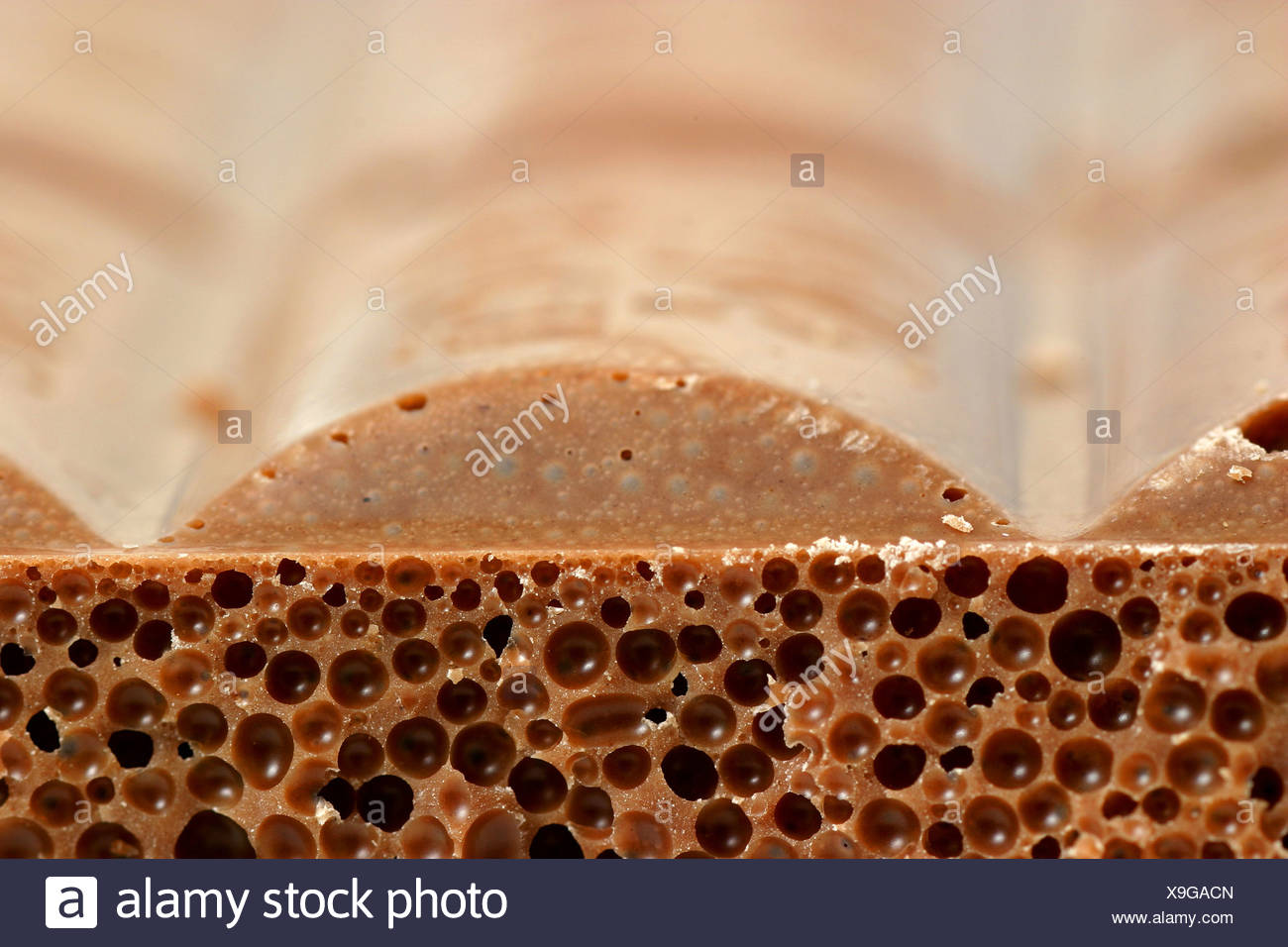 A close up of the side of a bar of milk chocolate with bubbles in it - Stock Image