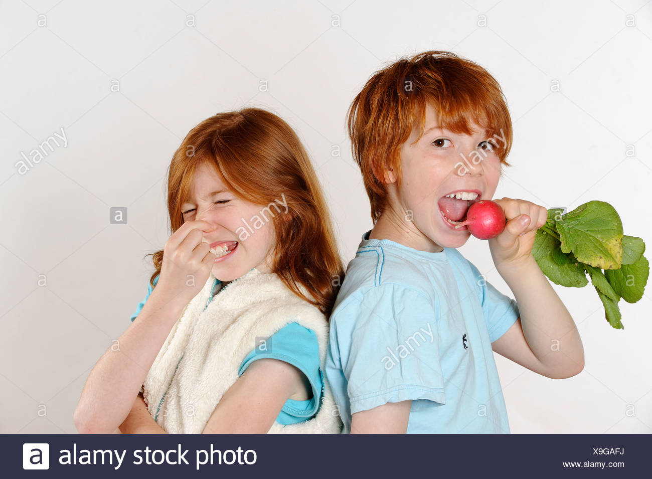 Boy eating radishes, girl rejecting raw food or vegetables - Stock Image