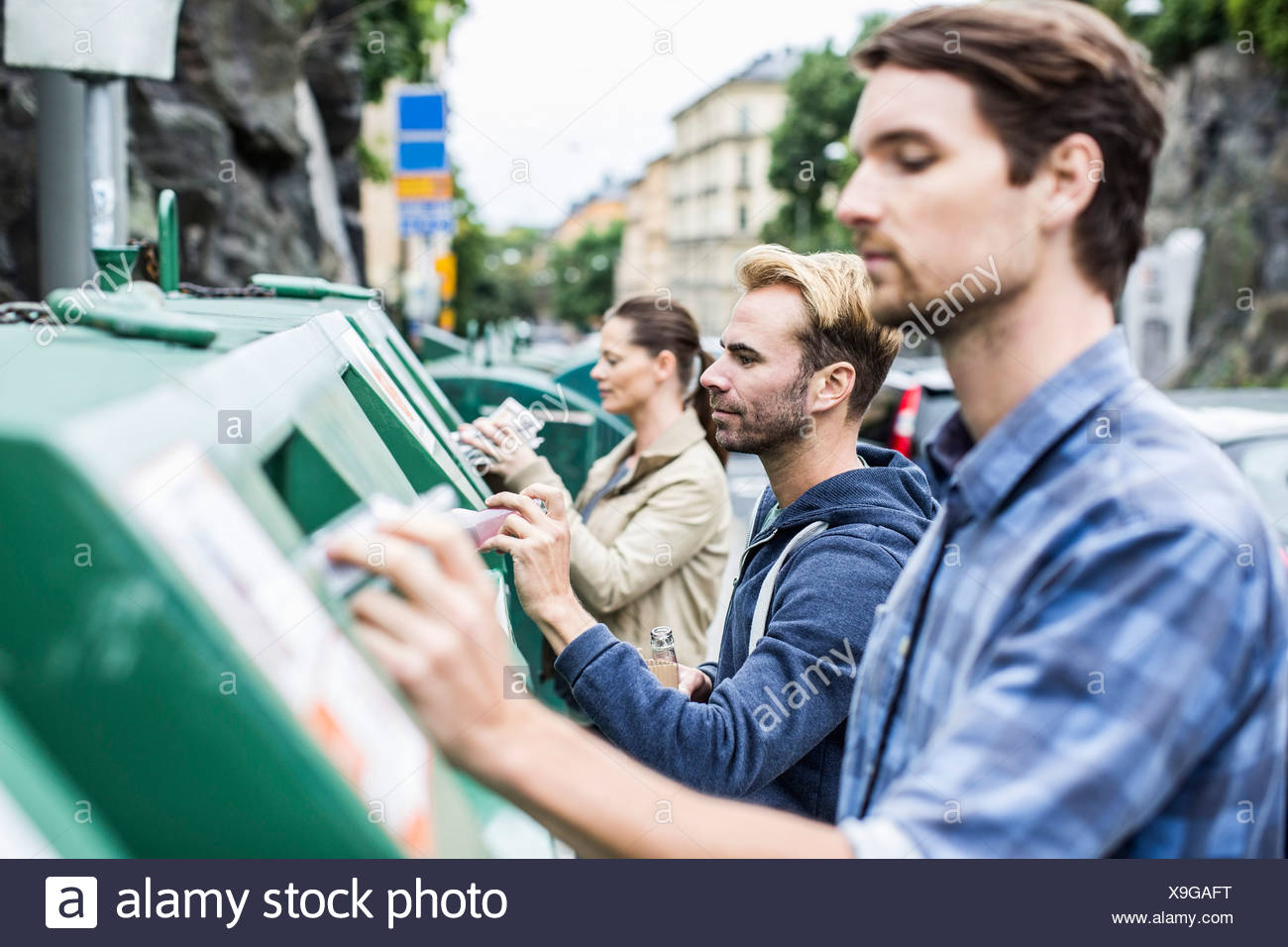 Friends putting recyclable materials into recycling bins - Stock Image