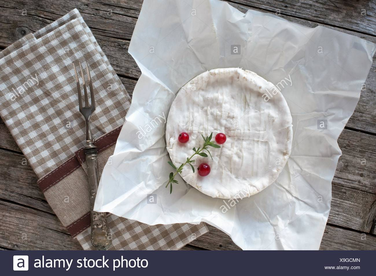 Camembert cheese on piece of paper, decorated with redcurrants and thyme. Stock Photo