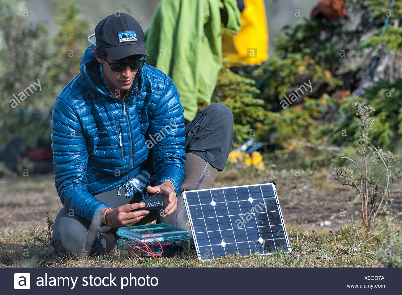 Videographer charging batteries using a solar charging system from our sponsors at Voltaic Systems. The solar charger was key equipment, every spare minute was spent charging batteries. - Stock Image
